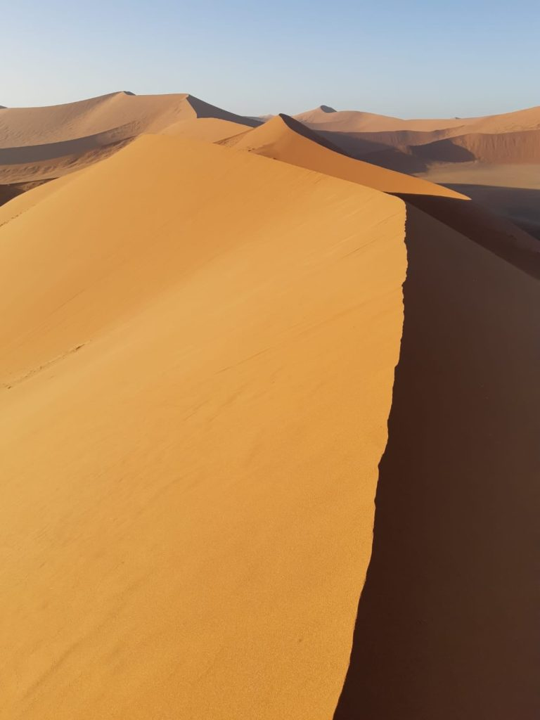 Východ slunce nad legendární dunou 45 v poušti Namib v Namibii